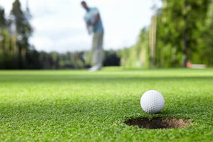 Close up of golfer making putt in hole